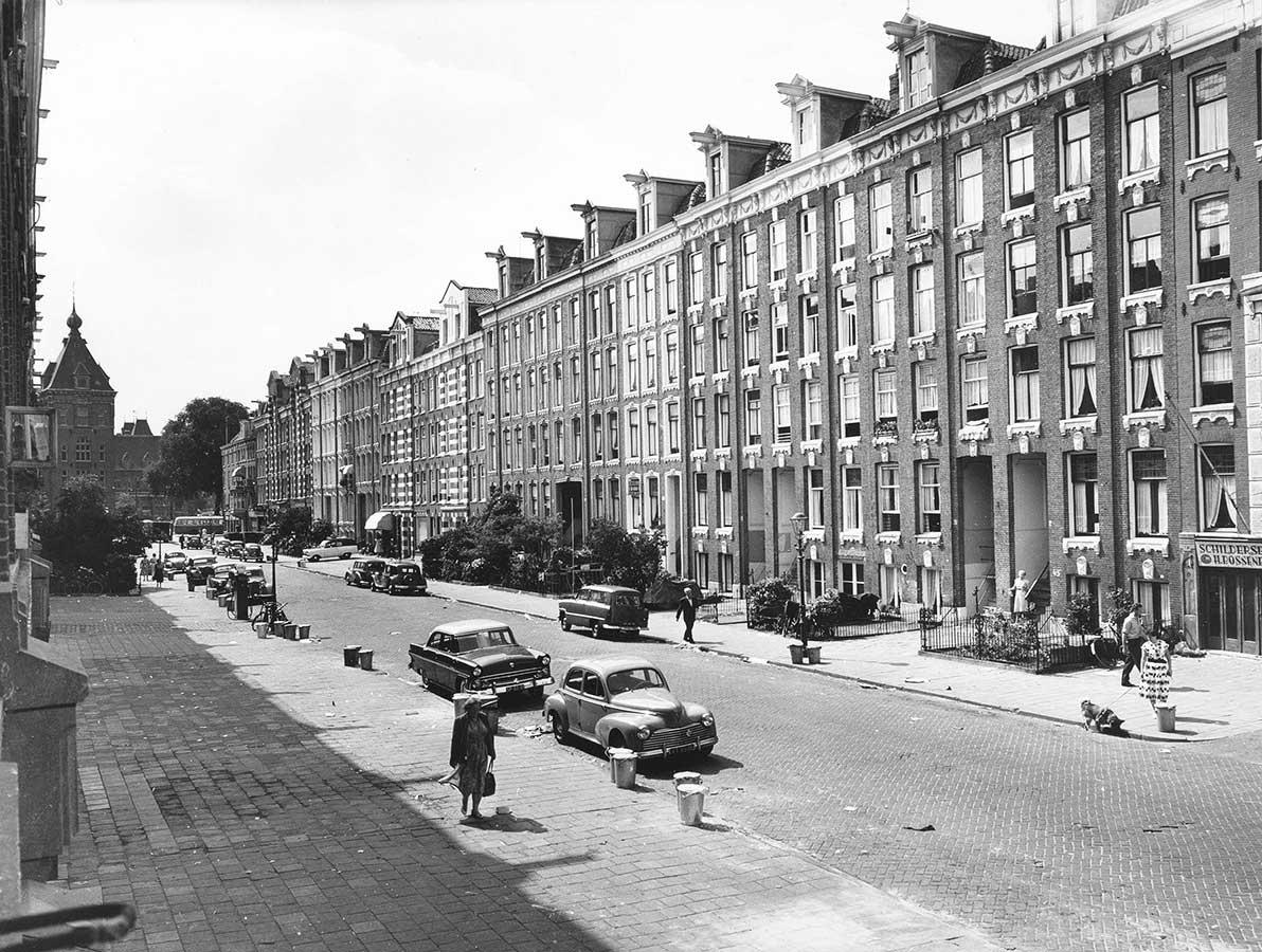 zwart-wit foto Commelinstraat 1-47 nog voor de asfaltering, toren Tropenmuseum in achtergrond