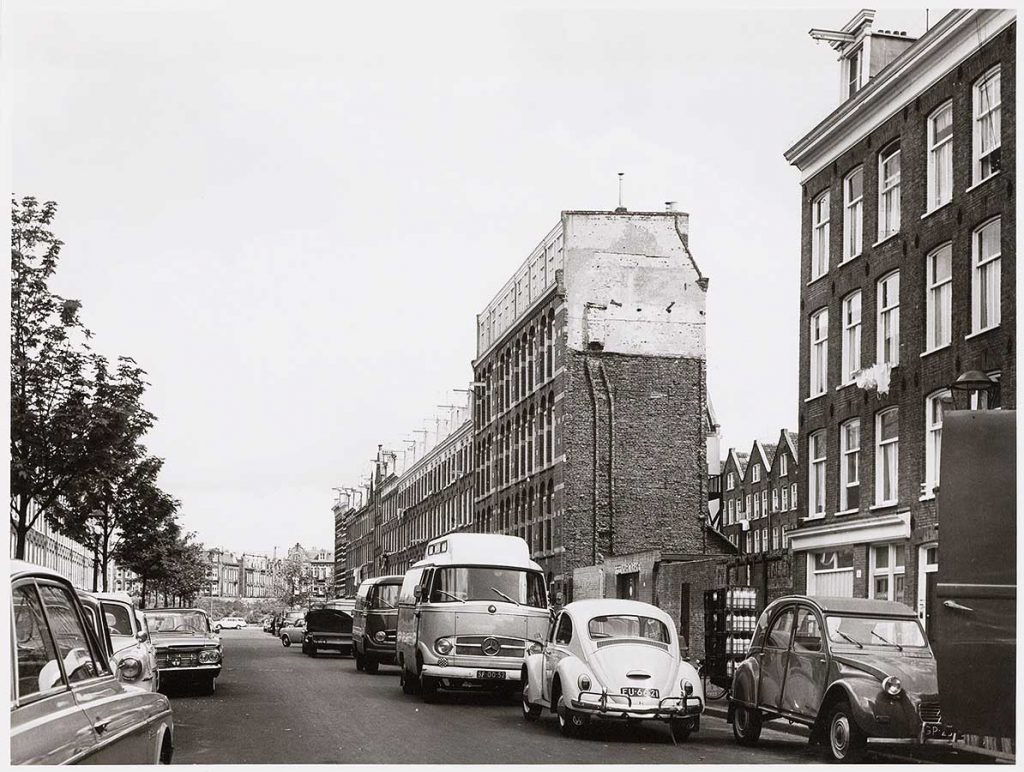 Oude zwart-wit foto van Commelinstraat met gapend gat in huizenrij