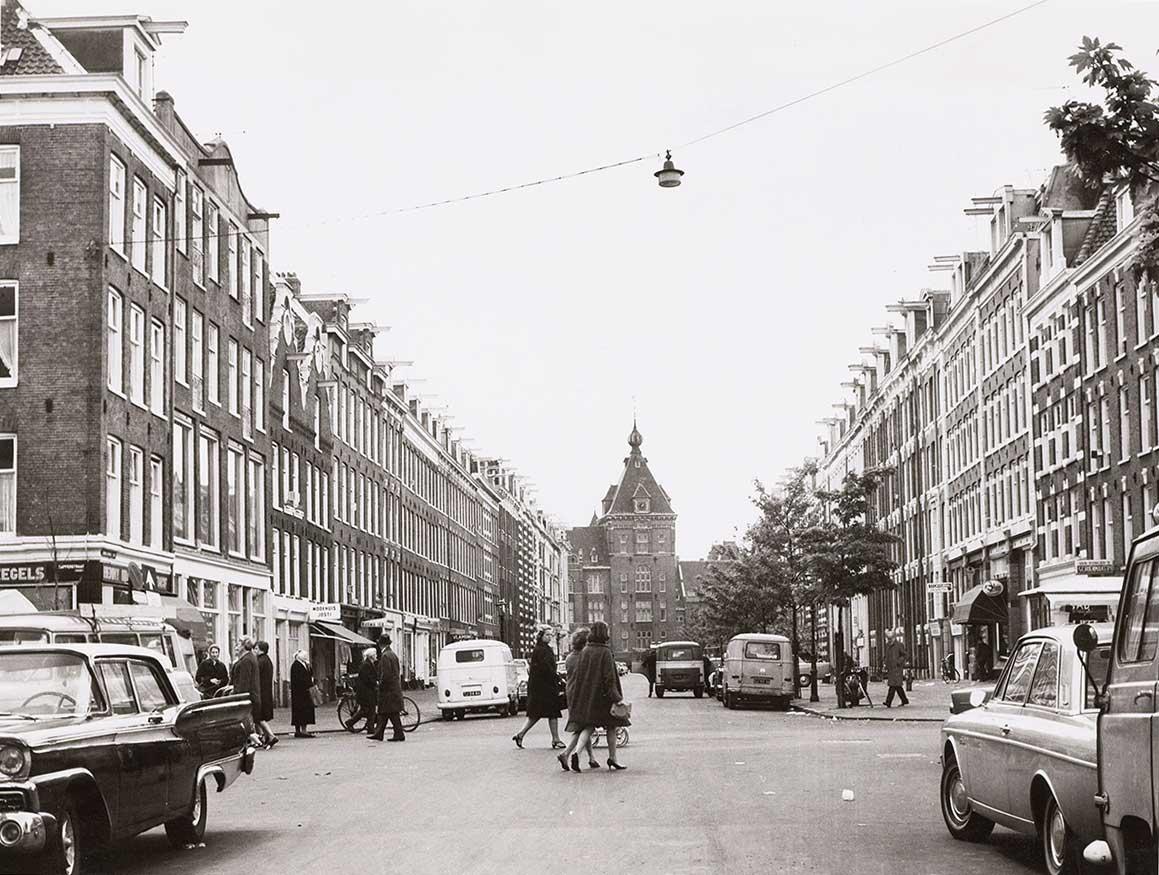 Zwart-wit foto Commelinstraat uit 1967 met toren Tropenmuseum op achtergrond. Aantal dames steken over.