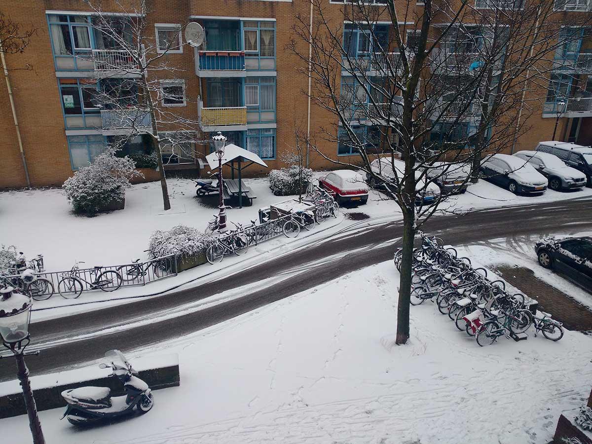 Besneeuwde Commelinstraat (bij knik in de weg), gezien vanaf 2e verdieping.