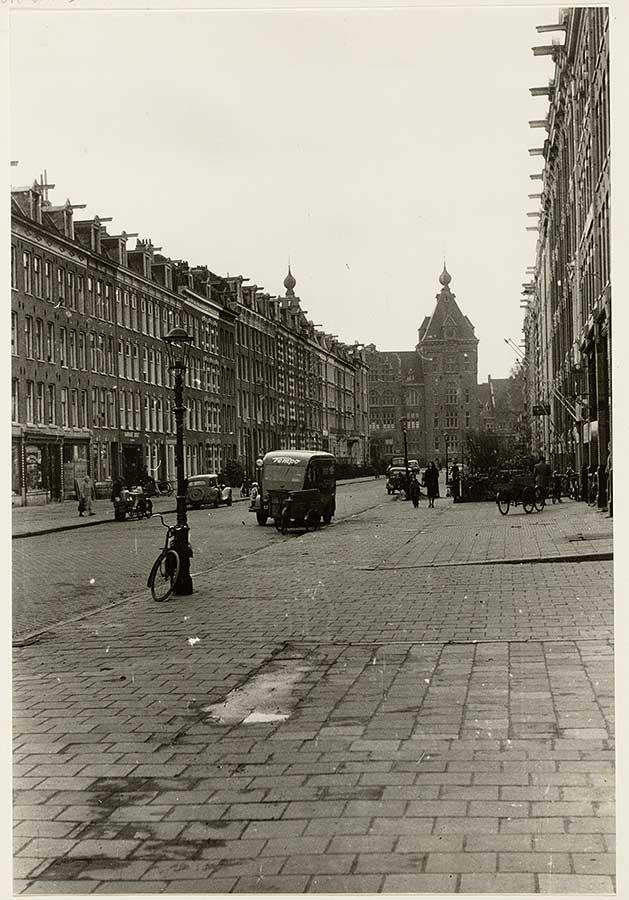 Oude zwart-wit foto van brede stoep zonder bomen in eerste deel Commelinstraat met uitkijk op toren van Tropenmuseum