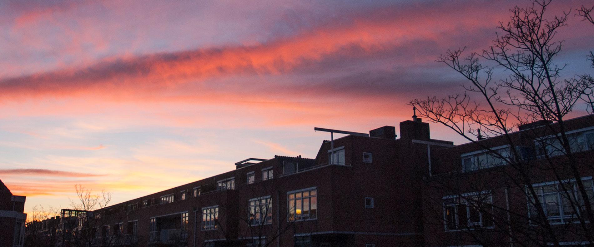 Zonsonderdagn met roze wolken in Commelinstraat
