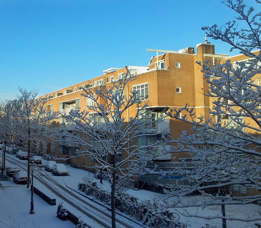 Fel winterlicht op besneeuwd appartementencomplex aan einde Commelinstraat. Besneeuwde boompjes op voorgrond. Foto geschoten vanaf 2e verdieping)