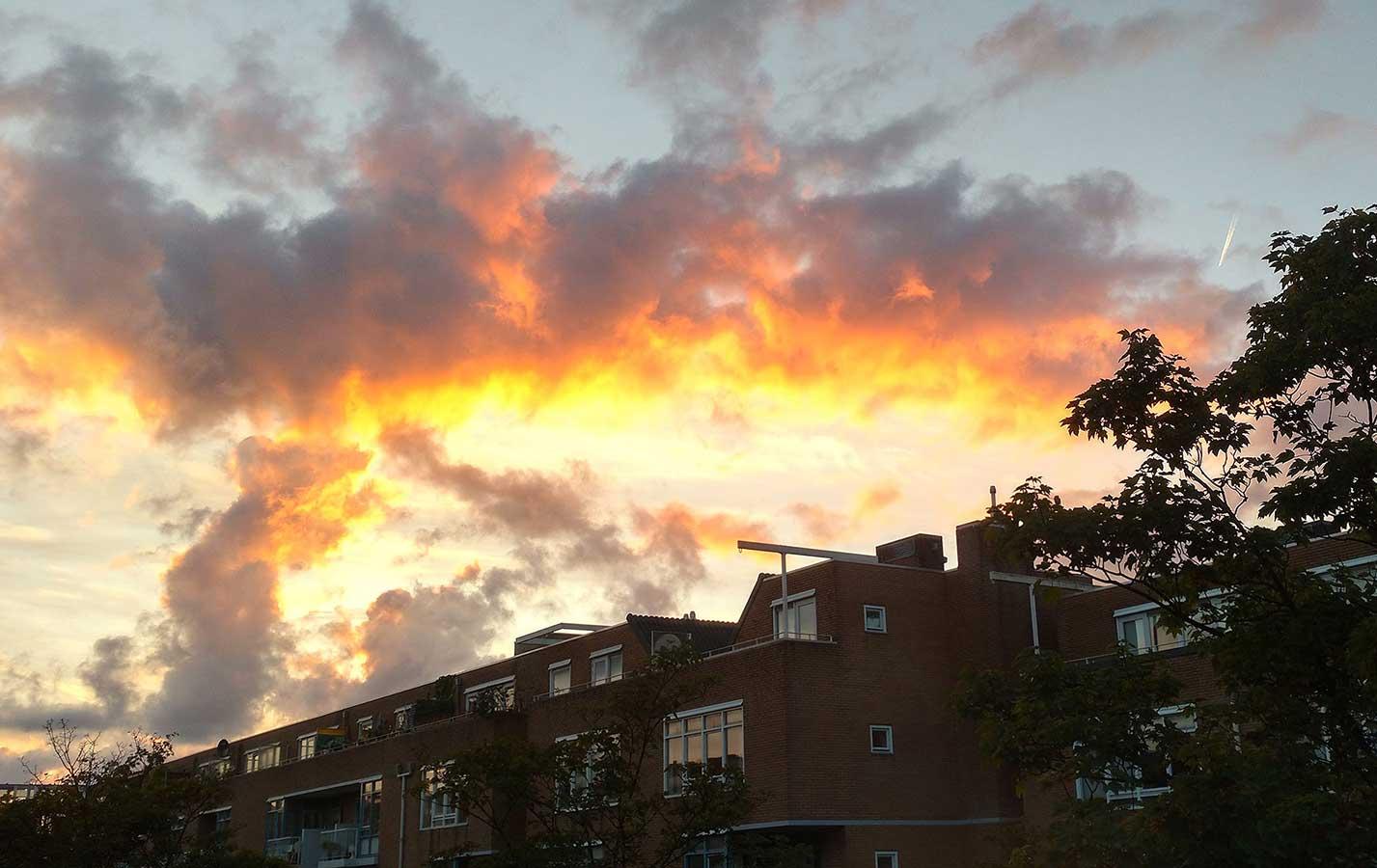 Oranje-gele wolken boven Commelinstraat tijdens zonsondergang in de herfst
