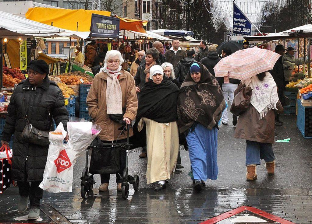 Verschillende nationaliteiten op een regenachtige Dappermarkt