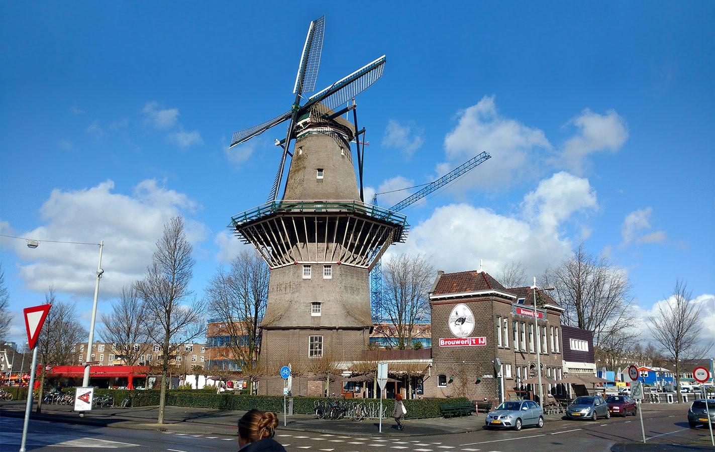Groothoek shot van molen met brouwerij 't IJ en een hijskraan op de achtergrond