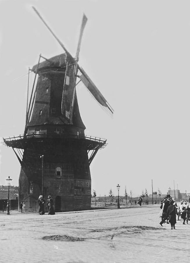 Oude foto van molen met wandelende mensen en zonder bebouwingen er om heen