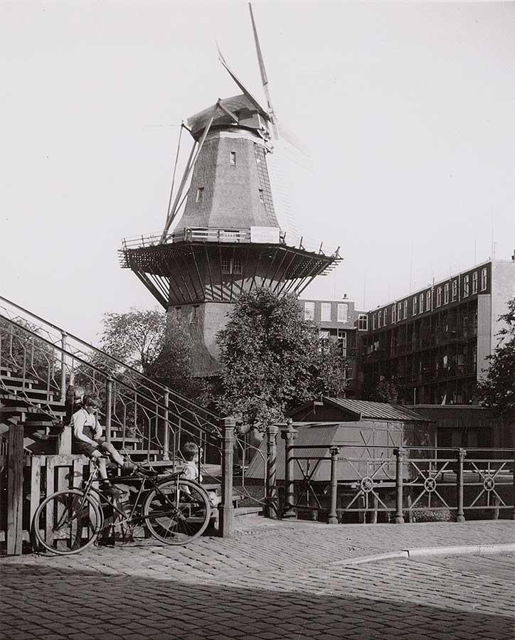 2 jongetjes op trap met geparkeerde fiets, molen de Gooyer op de achtergrond (juni 1930)