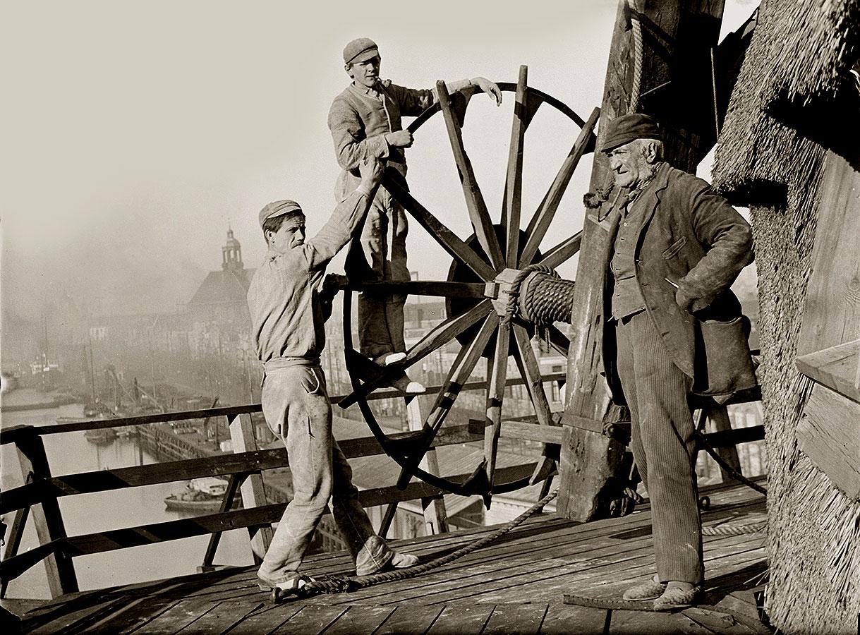 Molenaar Gerardus Hendrik de Boer en twee knechten op de molen met uitzicht op Oosterkerk