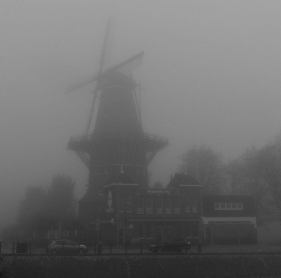 Zwart-wit foto van De Gooyer en brouwerij 't ij vanaf de brug gezien in dikke mist (2017)