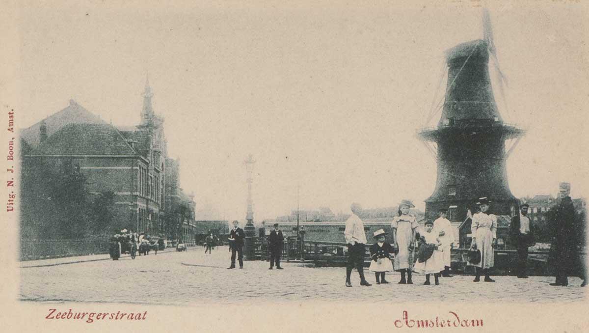 Oude briefkaart uit ca 1900 van zeeburgerstraat met rechts de molen en links de Funenkerk, mensen op straat poseren voor fotograaf