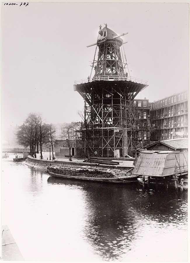 Skelet de Gooyer tijdens restauratie, 2 mannen bovenop de molen. Geschoten vanaf Crucuiuskade in 1930