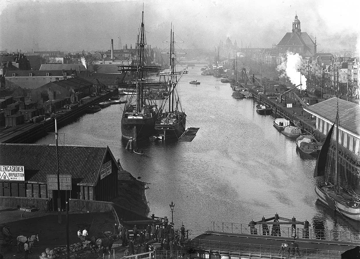 Uitzicht vanaf de Gooyer (1896) op lozingskanaal met schepen, Oosterkerk rechtsachter