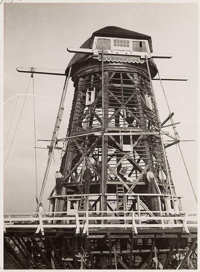 Houtengeraamte de Gooyer is zichtbaar terwijl werklui bezig zijn met de restauratie (1930)