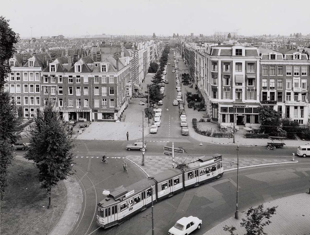 Begin Commelinstraat gezien vanaf KIT. Op Linneausstraat gaat tram voorbij.