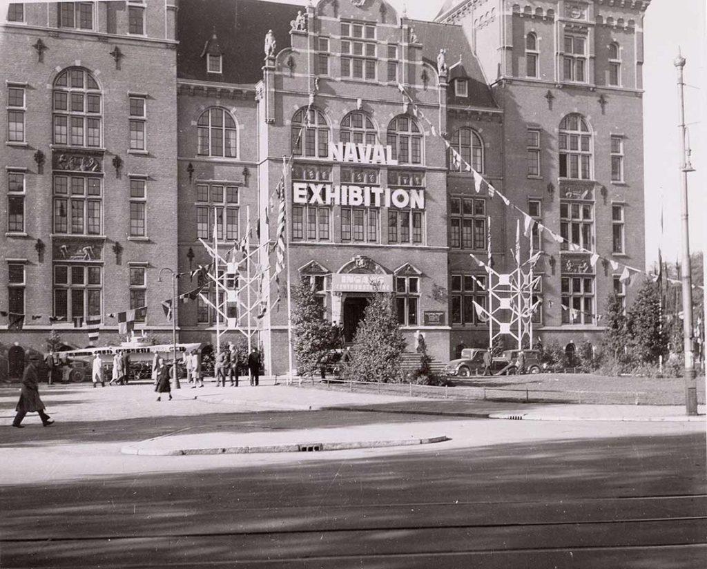 """Zijkant KIT met """"Naval Exhibition"""" belettering op gevel en versieringen (vlaggen) tijdens de bevrijdingsfeesten"""
