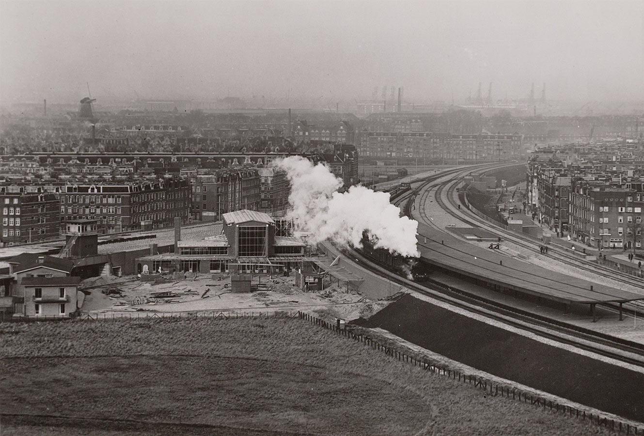 Foto vanuit hoog punt genomen met bouwwerkzaamheden nieuwe Muiderpoorstation. Bouwput waar nu Oostspoorplein is. Stoomlocomotief doet al perron aan met grote rookpluim. Rechts stuk Celebstraat te zien, links Pontanusstraat.