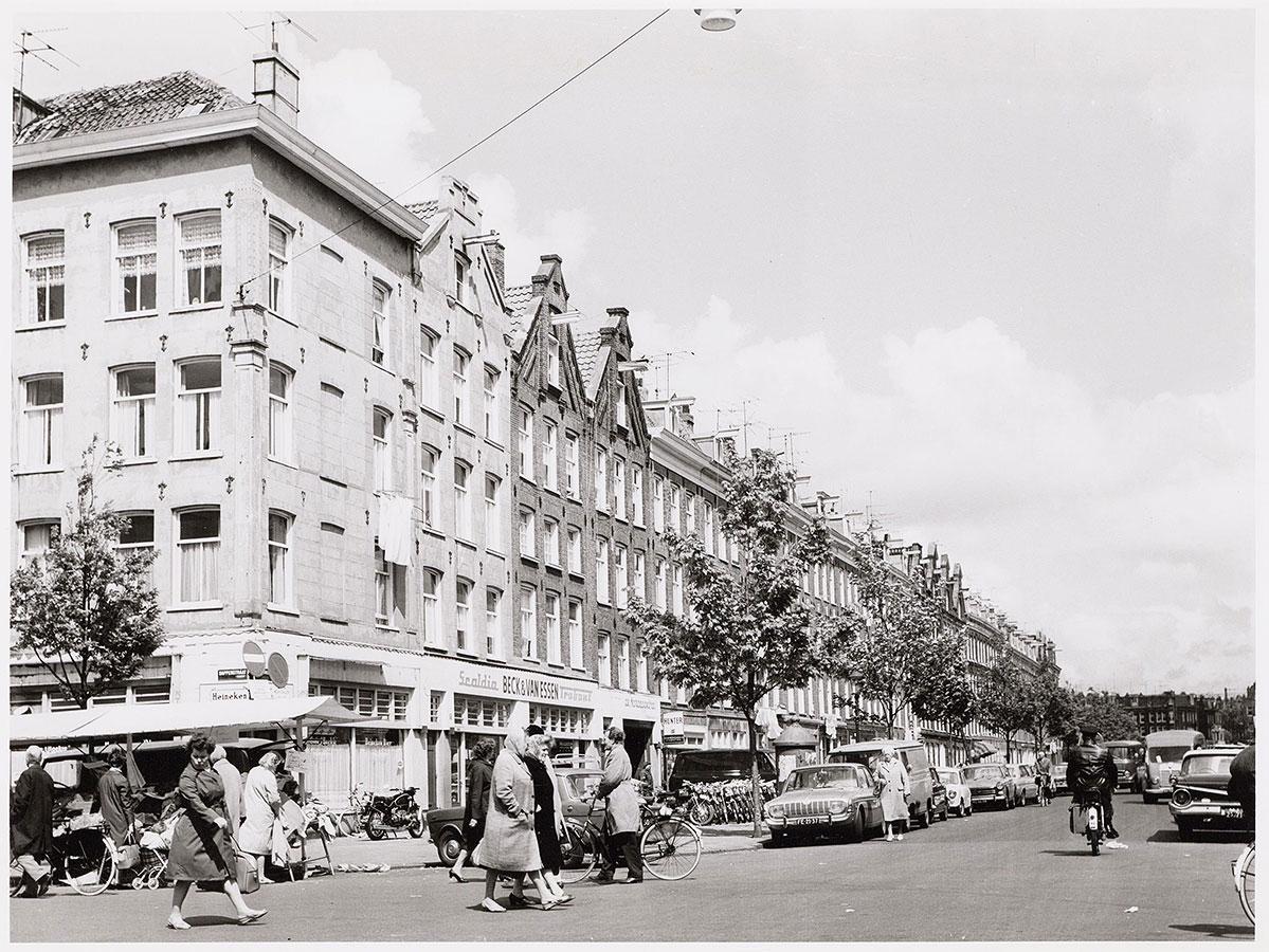 Commelinstraat gezien vanaf Dapperstraat waar mensen lopen.