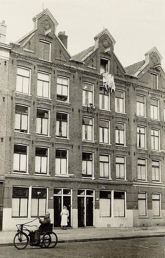 Oude foto van huizen in Commelinstraat. Man op aangepaste fiets op straat. Was hangt uit bovenste raam.