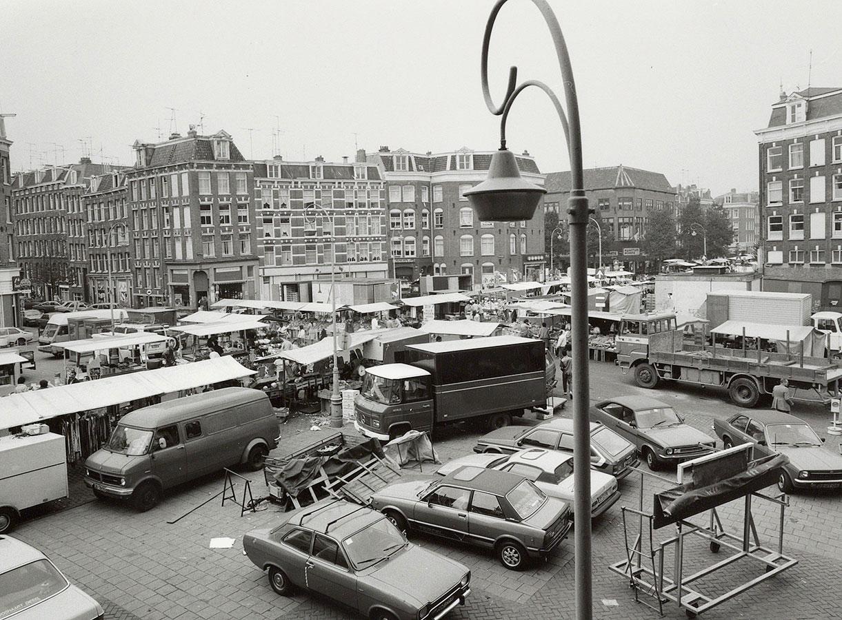 Dapperplein met Dappermarkt. Zicht op aantal geparkeerde (vracht)auto's en kraampjes. Foto op ongeveer 4 meter hoogte genomen.