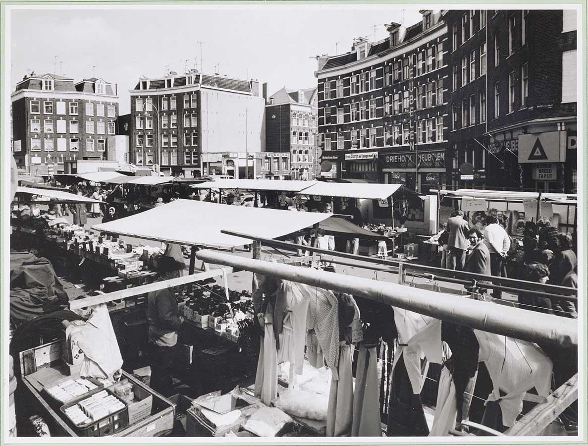 Dappermarkt kraampjes op Dapperplein. Camera kijkt over kraampjes heen