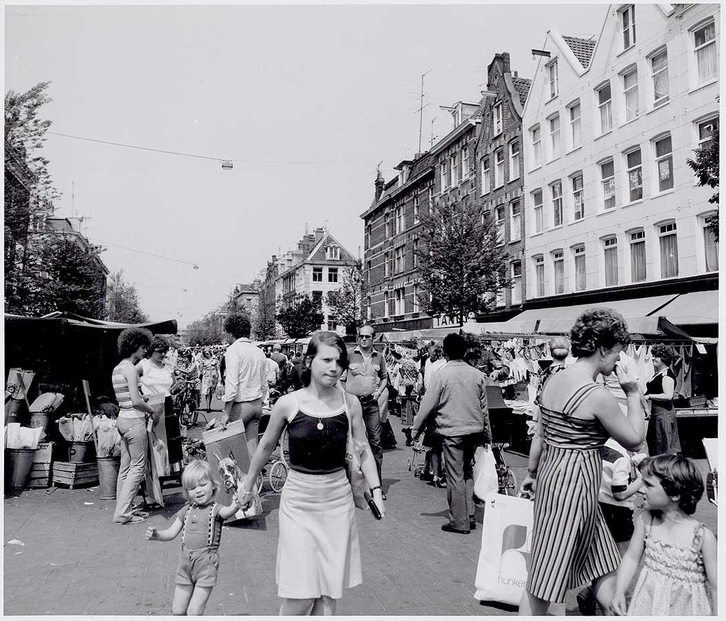 Dappermarkt met veel bezoekers, op de voorgrond jonge moeder met kind aan de hand