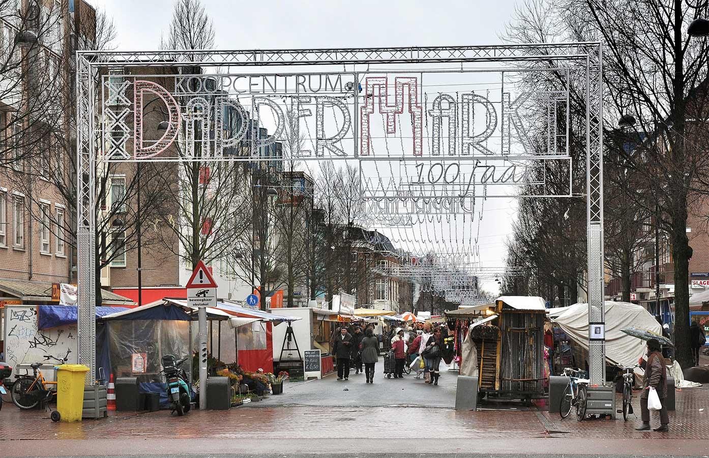 """Dappermarkt op regenachtige dag met tekstverlichting """"Koopcentrum DapperMarkt 100 jaar"""""""