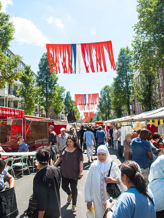 Dappermarkt met WK versiering in de vorm van oranje/rood/wit/blauwe vaandels boven de straat
