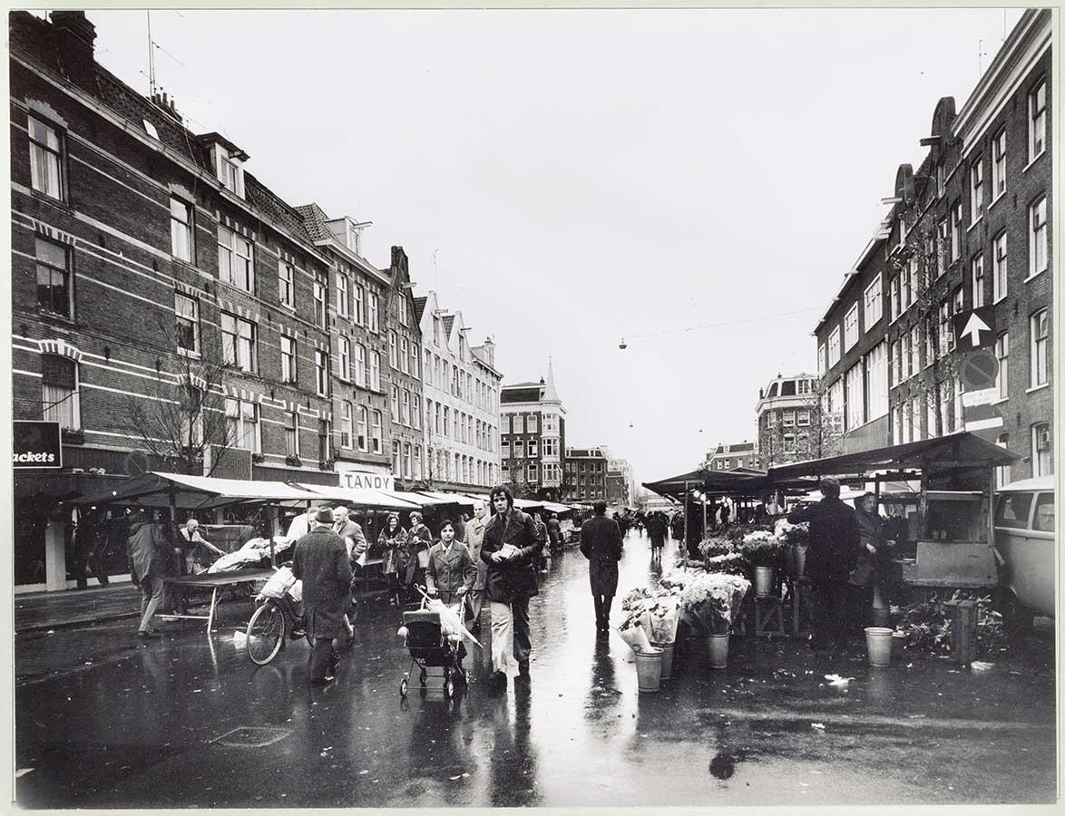 Regenachtige dag op de Dappermarkt. Stelletje met kinderwagen op voorgrond