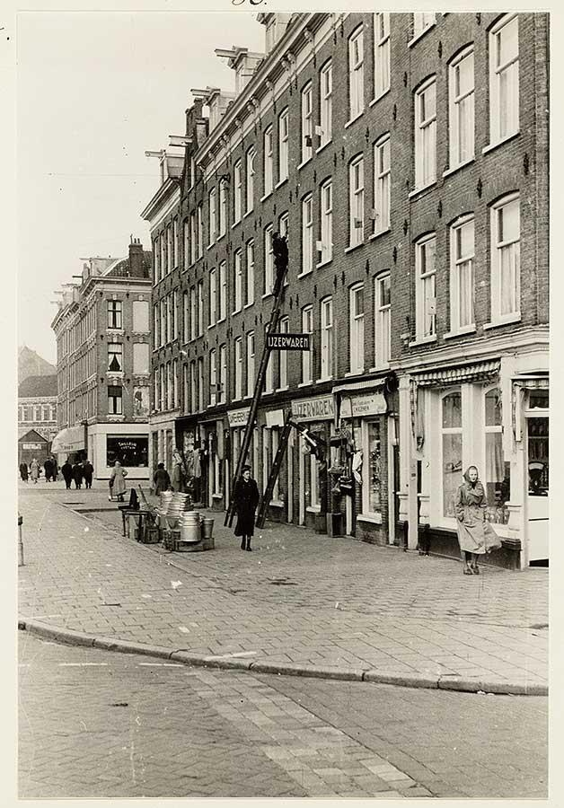 Oude foto van stoep in de Dapperstraat. Man op ladder voor raam 2 hoog (glazenwasser?). Voetgangers dragen lange jassen.