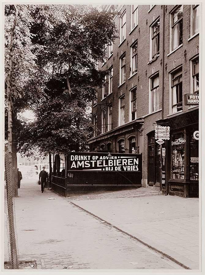 """Bord met tekst 'Drinkt op advies Amsterlbieren bij de Vries"""" op Dapperstraat 1. Terras achter het bord wordt overschaduwd door bomenpartij."""