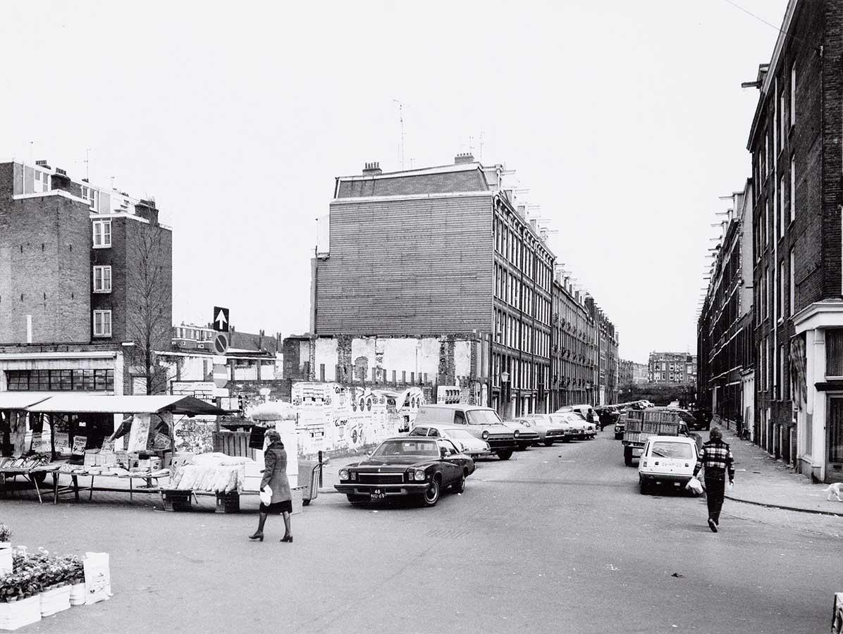 Door kale plek zijkant woningrij in Reinwardtstraat zichtbaar. Op de voorgrond in de Dapperstraat de Dappermarkt. Auto komt de Reinwardtstraat uitrijden.