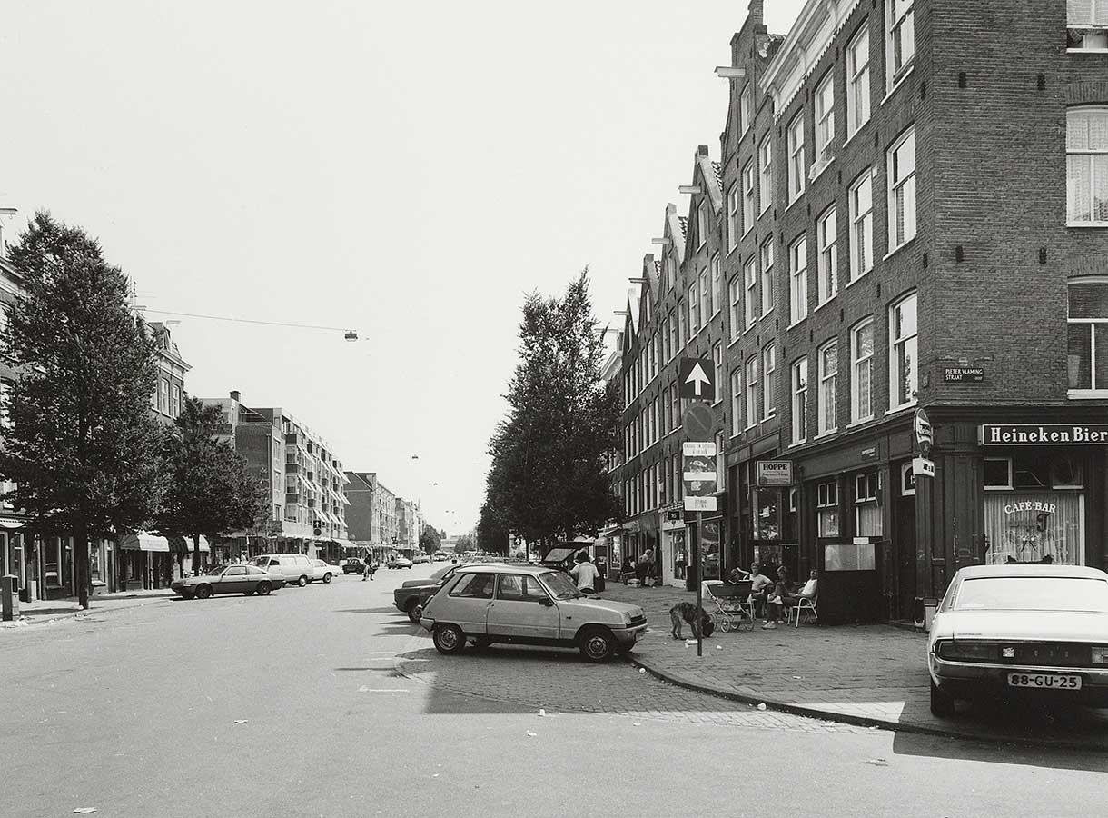 """Dapperstraat met geparkeerde auto's (geen markt) en paar mensen met hond en kinderwagen op terrasje hoek-bar """"Double J"""""""
