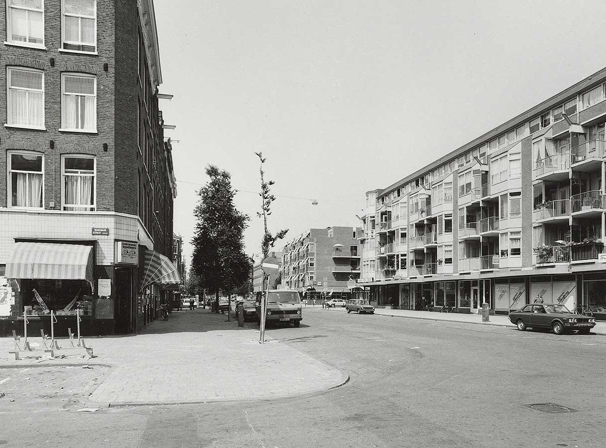 """Verlaten Dapperstraat met geparkeerde auto's. Op links op de hoek Wagenaarstraat/Dapperstraat zit """"In de warme broodhoorn"""""""