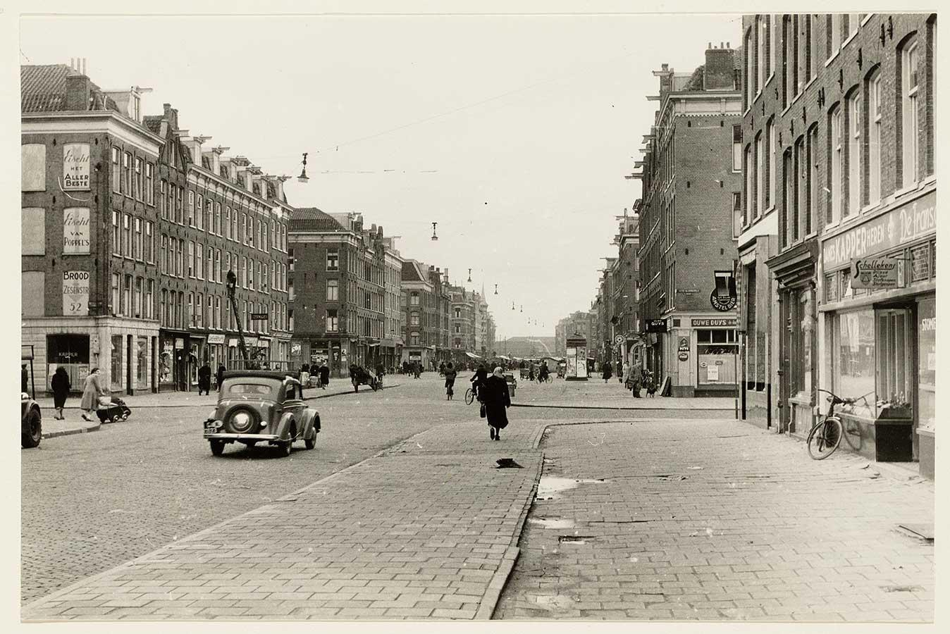 Dapperstraat zonder markt en nog niet geasfalteerd. Auto rijdt over de straat, vrouw loopt over brede stoep, vrouw met kinderwagen steekt over.