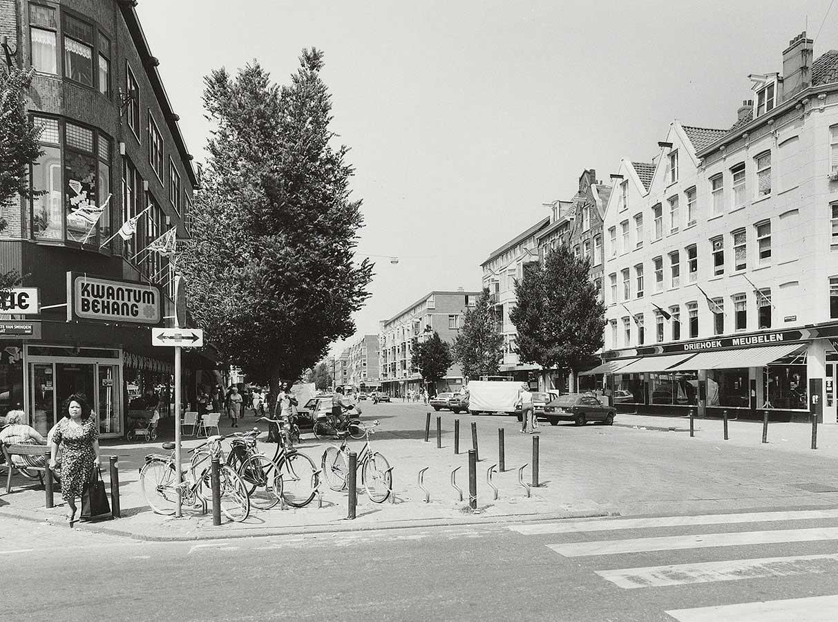 Dapperstraat vanaf 1e van Swindenstraat gezien. Links Kwantum Behang met op stoep een bankje en fietsenrekje met fietsen. Geen markt.