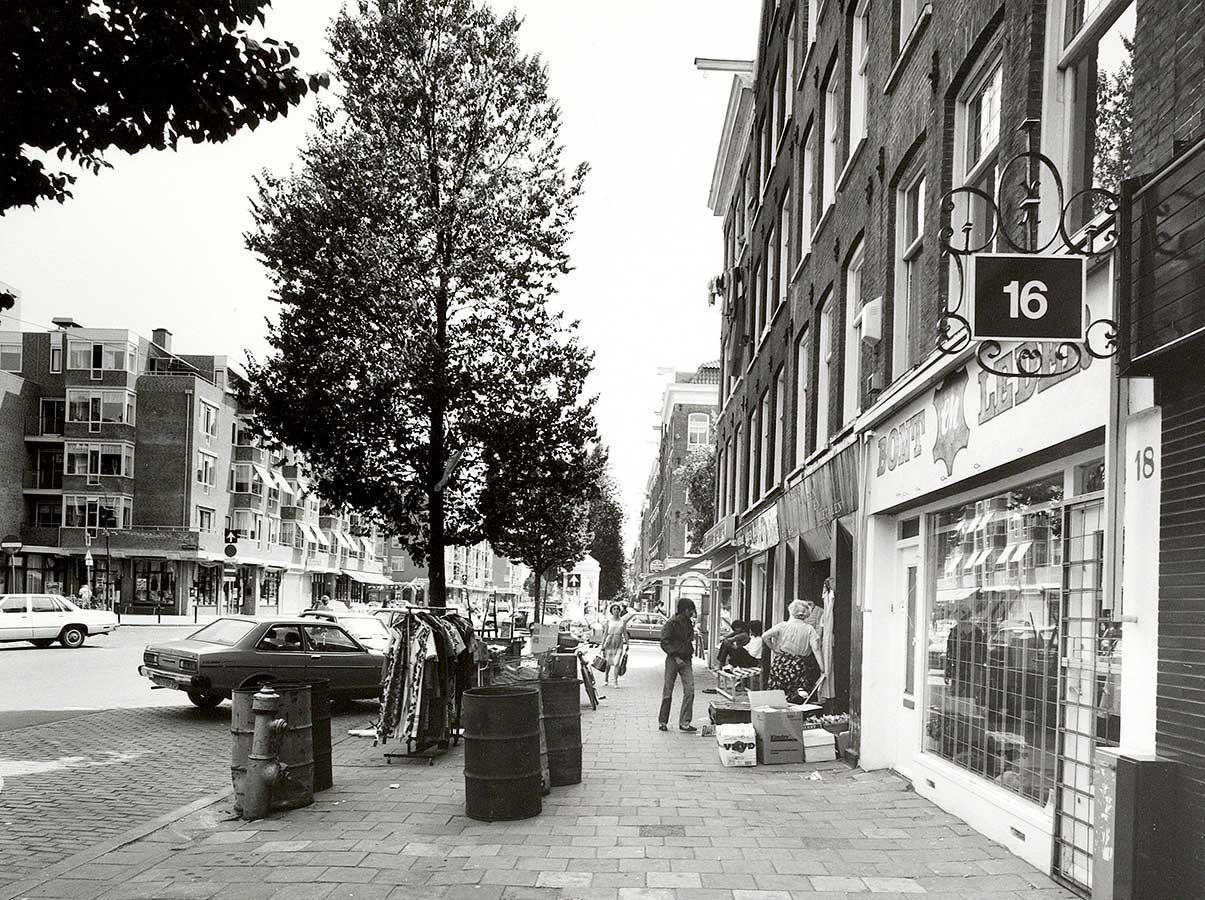 """Dapperstraat met rechts de zaak """"Bont en Leder"""", op de stoep een aantal vaten en rekje met kleding. Aantal mensen op de stoep. In de straat staan auto's geparkeerd, geen markt."""