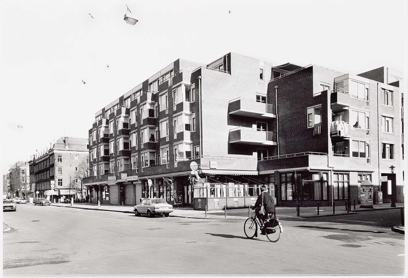 Nieuwbouwpand met in de hoe de Grote Pan. Geen markt op Dapperstraat, wel een eenzame fietser. Hier en daar een geparkeerde auto.