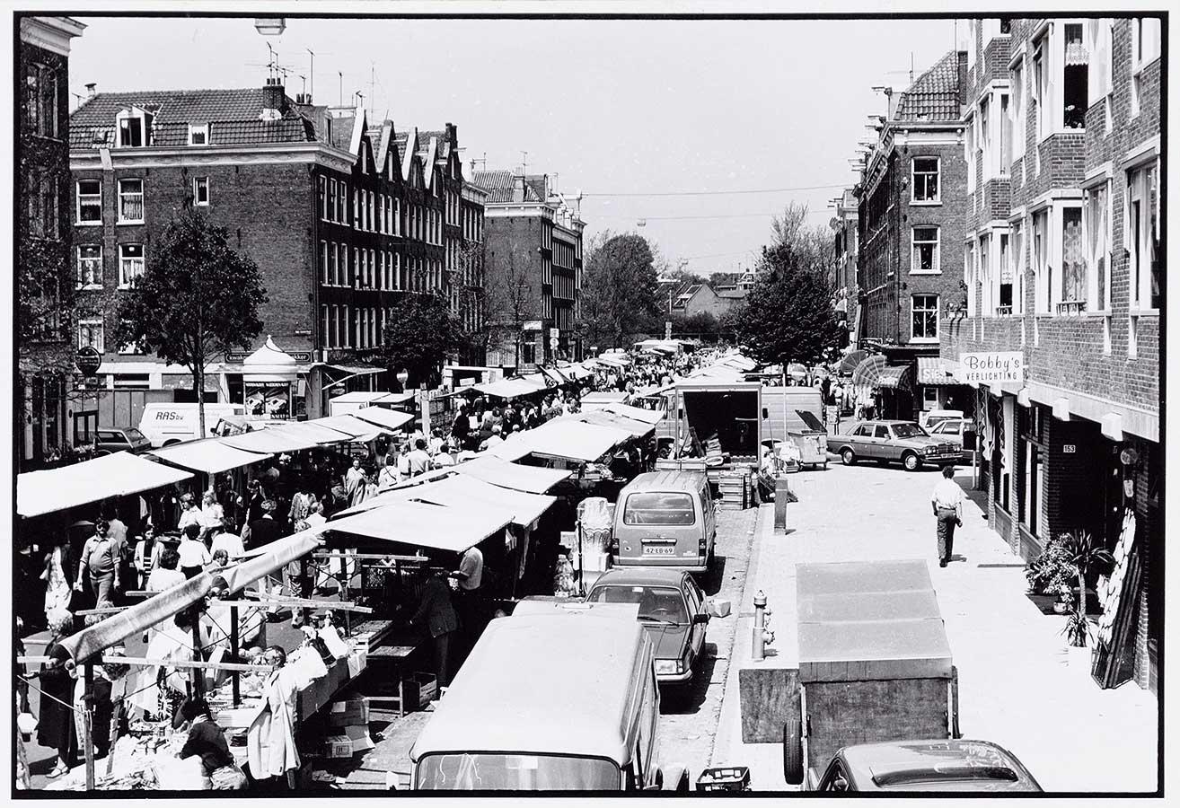 Dappermarkt, links op de foto de kraampjes, in het midden de geparkeerde auto's achter de kramen, rechts de stoep
