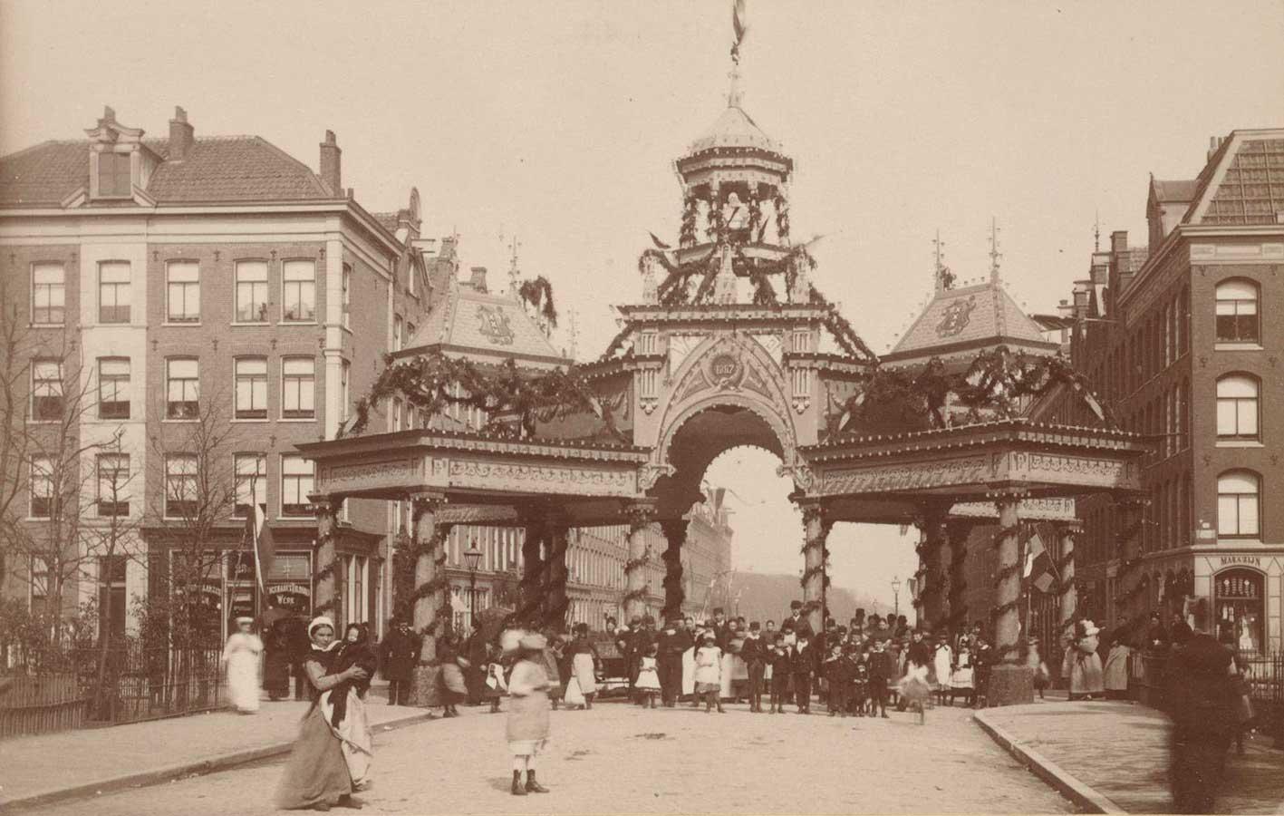 Erepoort op het kruispunt van Commelinstraat en Dapperstraat. Veel mensen poseren voor de poort