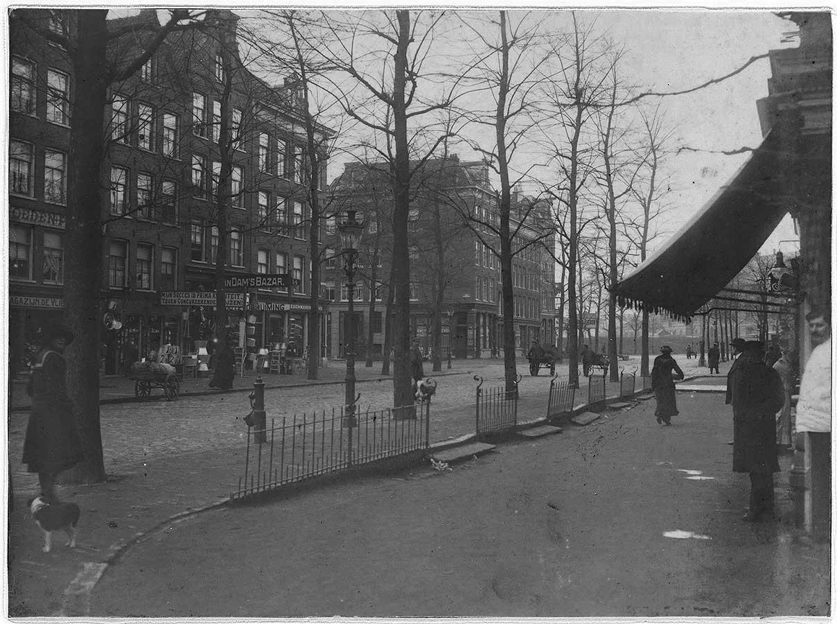 Oude foto uit 1932 van Dapperstraat in de winter (geen sneeuw) zonder markt maar met hier en daar een ventwagen die over de straat rijdt. Meisje met hondje kijkt om. Kleine hekwerkjes scheid de stoep in twee delen.