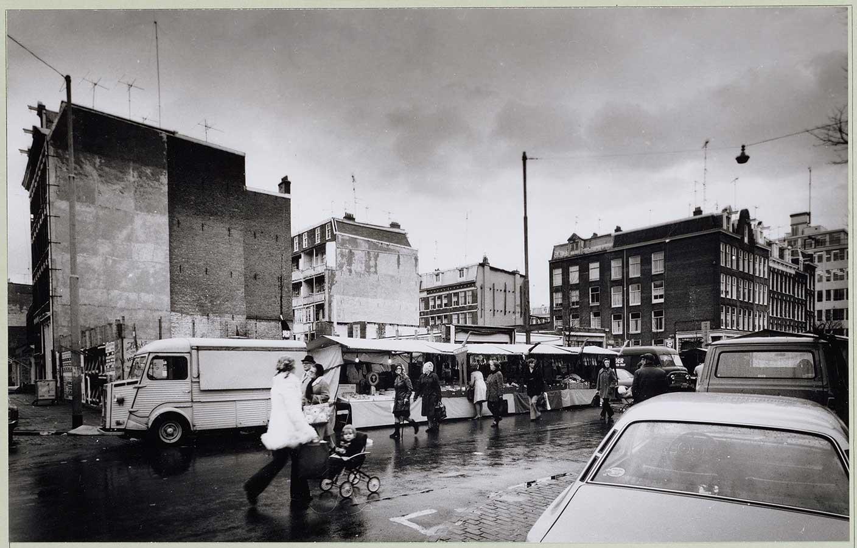 Veel gesloopte woningen. Links de kale zijkant van huizen in de Pieter Nieuwlandstraat en in het midden uitzicht op dezelfde soort kale muren van huizenrijen in de volgende straten. Op de voorgrond Dappermarkt op een regenachtige septemberdag.