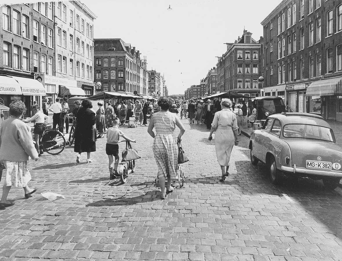 Dapperstraat toen er nog kinderkopjes lagen i.p.v. asfalt. Markt, kijken op rug van kind met step en moeder met kinderwagen. Rechts een geparkeerde Duitse auto waar geen kraampjes staan.