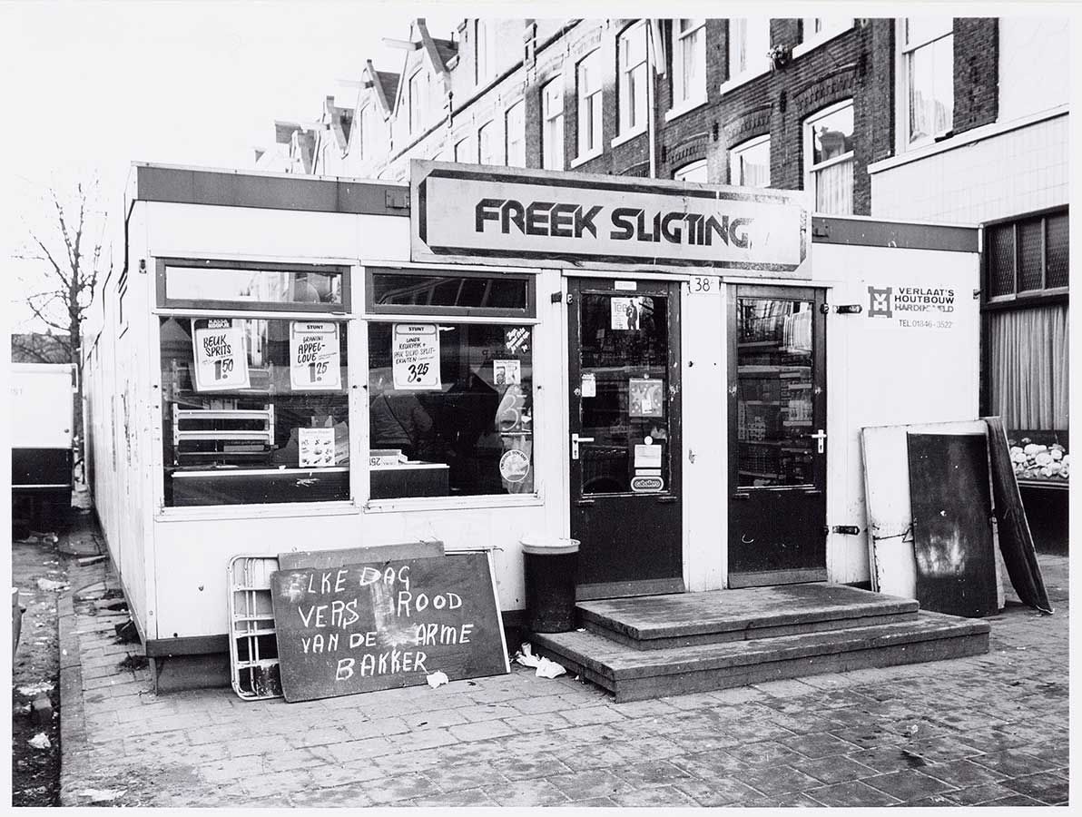 Freek Sligting groentehal in een soort keet. Op uithangbord zijn letters weggeveegd waardoor te lezen valt: 'Elke dag vers rood van de arme bakker'.