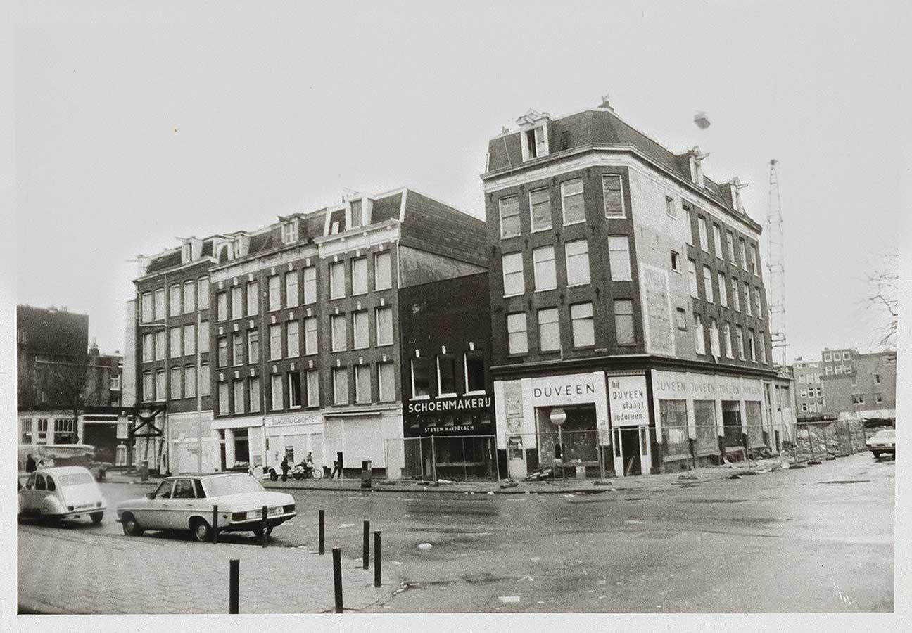 Dapperstraat 72-86 in 1983, rechts ingang Pieter Nieuwlandstraat met op achtergrond kraan op afbraakterrein.