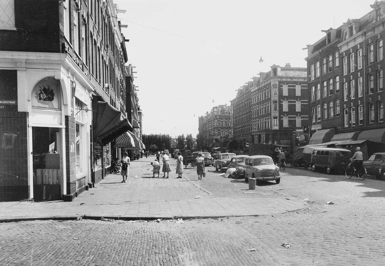 Dapperstraat ter hoogte Pieter Nieuwlandstraat gezien richting Wijttenbachstraat. Aantal vrouwen op brede stoep. In Dapperstaat staan veel geparkeerde auto's aan weerszijden.