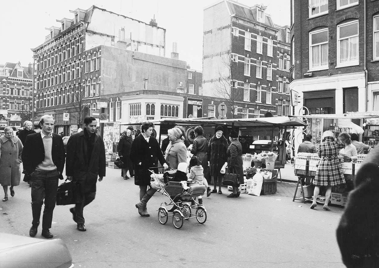 Dapperstraat met markt en publiek, o.a. vrouw met kinderwagen. Rechts Reinwardtstraat