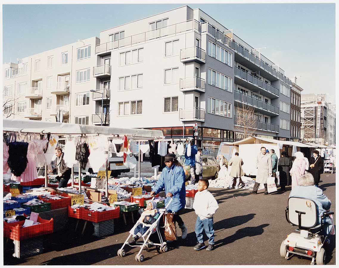 Nieuwbouwpand hoek Dapperstraat/Von Zesenstraat met Dappermarkt in de Dapperstraat. Vrouw met kinderwagen op de voorgrond.