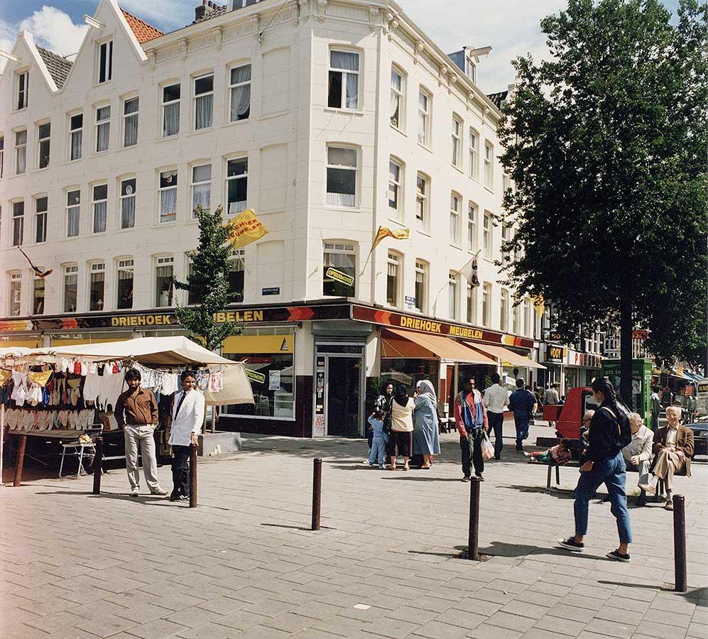 In het midden van de foto de ingang van Driehoek Meubelen (nu KFC). Multicultureel publiek op straat. Ook nog stukje groene PTT telefooncel te zien.