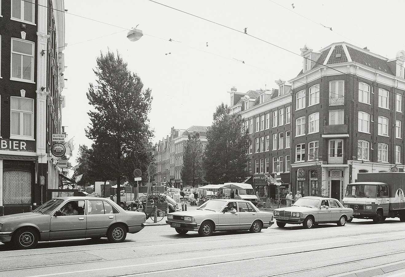 Mauritskade met rij auto's, daarachter Dapperstraat met markt